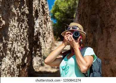 Young woman taking pictures of a beautiful scene