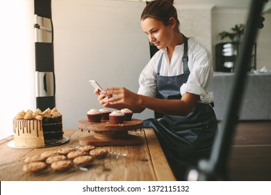 Young woman taking pictures of a cake in the kitchen. Female baker capturing photos of pastry items with her mobile phone.