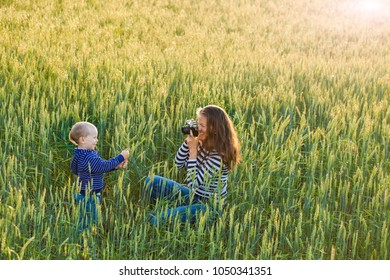 Young woman taking pictures  child in field