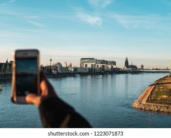 Young Woman taking pictures of Cologne's skyline with her smartphone