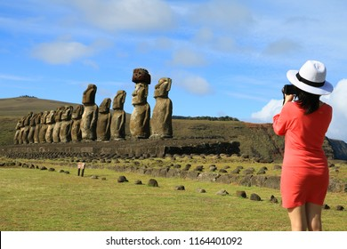 Young woman taking pictures of the famous Moai statues at Ahu Tongariki on Easter Island, Archaeological site in Chile
