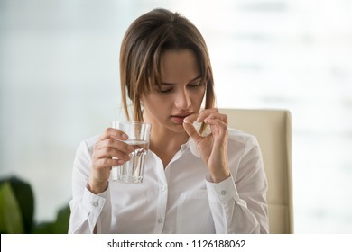 Young woman taking pill to relieve headache or ilness symptoms, stressed businesswoman holding antidepressant or painkiller medication and glass of water, meds for fast pain relief at work concept