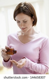 Young woman taking pills from bottle at home