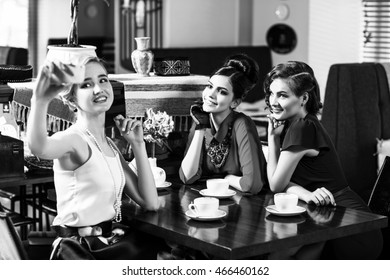 Young woman taking selfie at cafe together