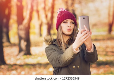 Young woman taking a selfie or filming a video or vlog on smartphone in park in autumn. Natural lighting, retouched, filter applied.