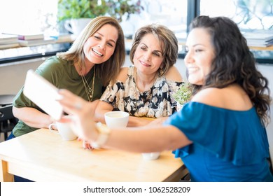 Young woman taking selfie with friends at coffee shop