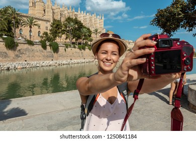 Young woman taking a selfie in front of Palma Cathedral
