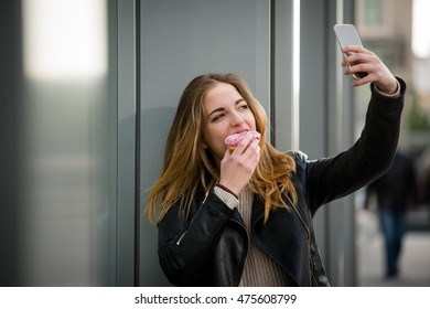 Young woman taking selfie with mobile phone while eating donut in street