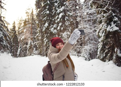 Young woman taking selfie on a background of snow covered winter pine forest. Frosty weather. Big pines. Winter holidays