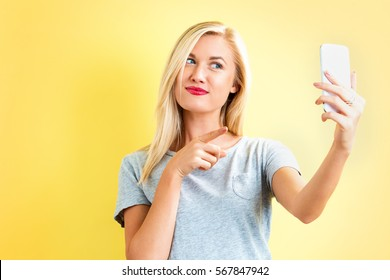 Young woman taking a selfie on a yellow background