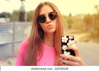 Young woman taking a selfie outdoors on sunny summer day. Photo toned style Instagram filters