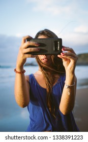 Young woman taking a selfie photo with her smartphone camera on summer vacation at the beach.