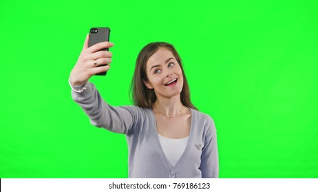 Young Woman Taking Selfie and pulling faces for the photo on Green Screen Background