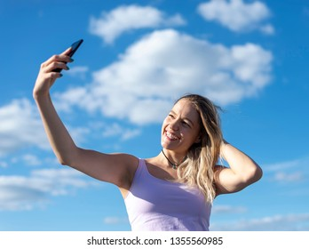 young woman taking selfie with smartphone