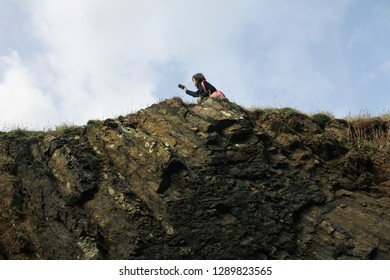 young woman taking selfies with the landscape on the edge of the cliff