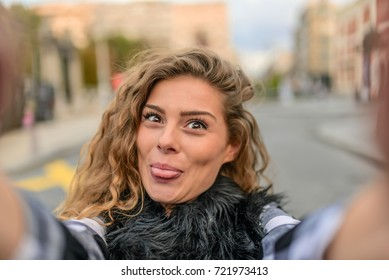 Young woman taking a selfie.Smiling woman taking a selfie photo.