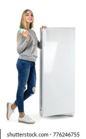 Young woman taking yogurt from refrigerator on white background