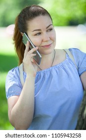 Young woman talking by cellphone on nature, portrait
