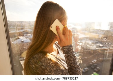 The young woman is talking by phone near the window with view on the city