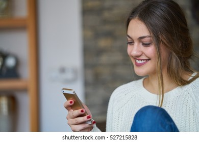Young woman talking cell phone in loft apartment