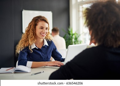 Young woman is talking to her client in the office, colleague sitting behind her