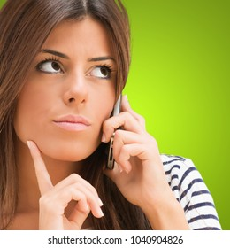 Young Woman Talking On Cellphone against a green background