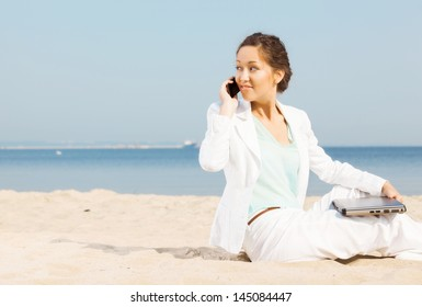 Young woman talking on cellphone on a beach