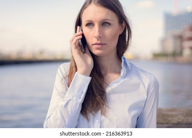 Young woman talking on her mobile phone listening to the conversation with a serious expression as she stands outdoors against a river backdrop