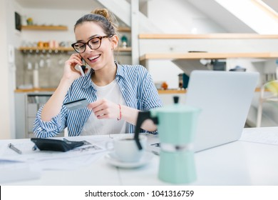 Young woman talking on mobile phone and  using credit card