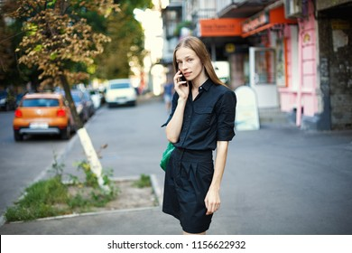 young woman with talking on mobile phone on city background.