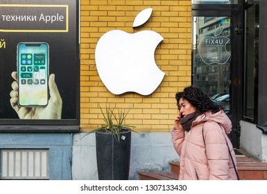 young woman talking on mobile phone walking past the Apple logo seen outside of a mobile repair service center in Kiev,Ukraine, 07 February 2019.