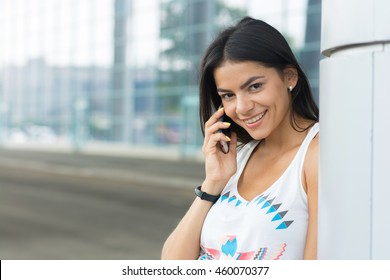 Young woman talking on mobile phone at the street