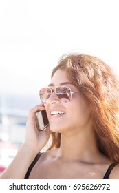 Young woman talking on the mobile phone at the boat pier