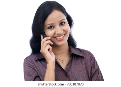 Young woman talking on mobile phone against white