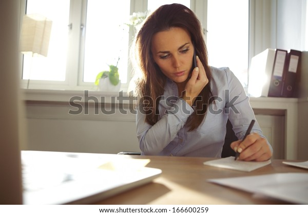 Young woman talking on mobile phone and writing notes while sitting at her desk. Pretty caucasian female working in home office.