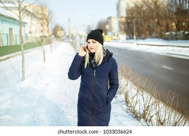 Young woman talking on phone on the street with snow in background