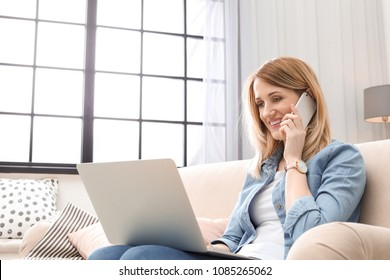 Young woman talking on phone while working with laptop on sofa in home office