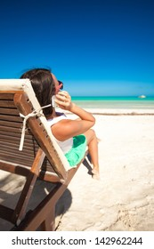 Young woman talking on the phone while sitting on a beach lounger