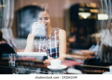 Young woman talking on phone and using tablet computer in coffee shop