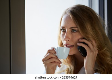 Young woman talking on the phone and drinking coffee at the window