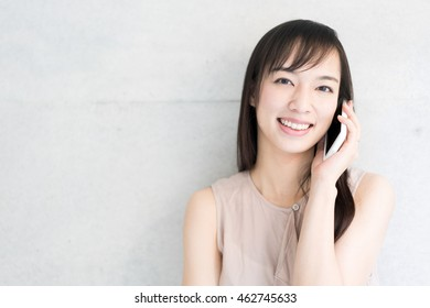 Young woman talking on a phone against concrete wall
