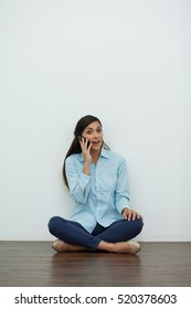 Young Woman Talking on Phone and Sitting on Floor