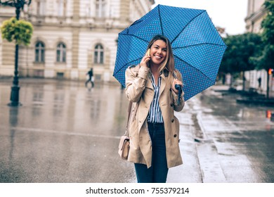 Young woman talking on the phone on a rainy day