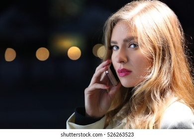 Young woman talking on smart phone in street at evening
