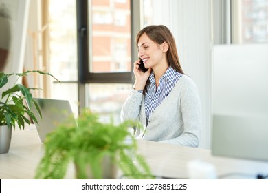 Young woman talking over smartphone while sitting in office