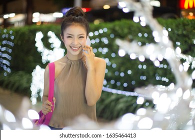 Young woman talking with a smart phone on a city street.