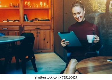 Young woman talking in video chat with her sister via digital tablet while sitting in her favorite cafe and drink delicious green tea, female watching movie on touch pad while breakfast in coffee shop