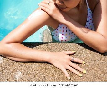 Young woman tan skin with healthy skin applying sunscreen to shoulder which she is  protection of sunburn and cancer prevention concept.