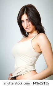 young woman in tanktop looking down