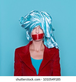 Young woman with taped mouth with towel on head in studio